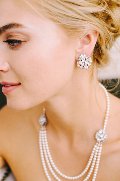 Gazing off, a woman is wearing her sparkling stud earrings made with various sizes of Swarovski clear crystals and pale ivory pearls on a rhodium plated filigree. Out of focus, is a matching pearl necklace that consists of two filigrees matching the earrings, one on each side of necklace along with three strands of crystals and pearls dangling below. Made by Sara Gabriel.