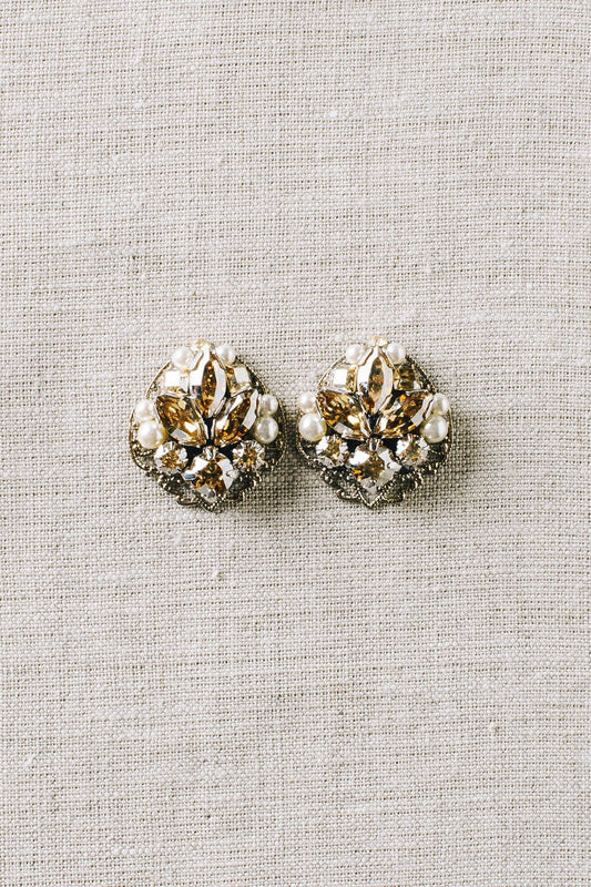 A pair of stud earrings that consist of various sizes of Swarovski champagne crystals and pale ivory pearls on a rhodium plated filigree against a canvas background. Made by Sara Gabriel.