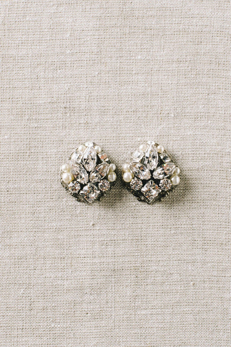 A pair of stud earrings that consists of various sizes of Swarovski clear crystals and pale ivory pearls on a rhodium plated filigree against a canvas background. Made by Sara Gabriel.