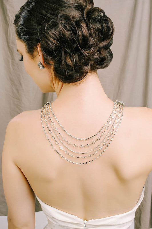 With her back turned completely, a woman is wearing a necklace that has five strands in the back. The strands use Swarovski clear and crystal-set chain. With her head turned slightly to the left, you can see her Swarovski pearl and crystal stud earring. Sara Gabriel.