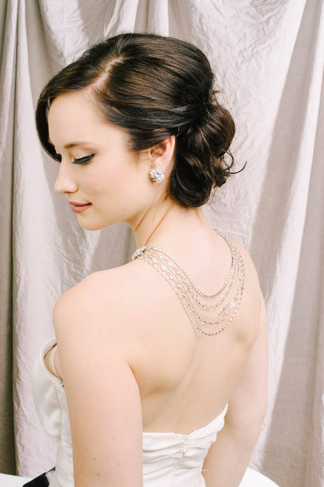 A bride with her back turned to the side displaying her Swarovski crystal and pearl stud earrings, along with her multiple strand necklace. The necklace has 5 strands on the hanging down the back, which include Swarovski clear and crystal-set chain. Sara Gabriel.