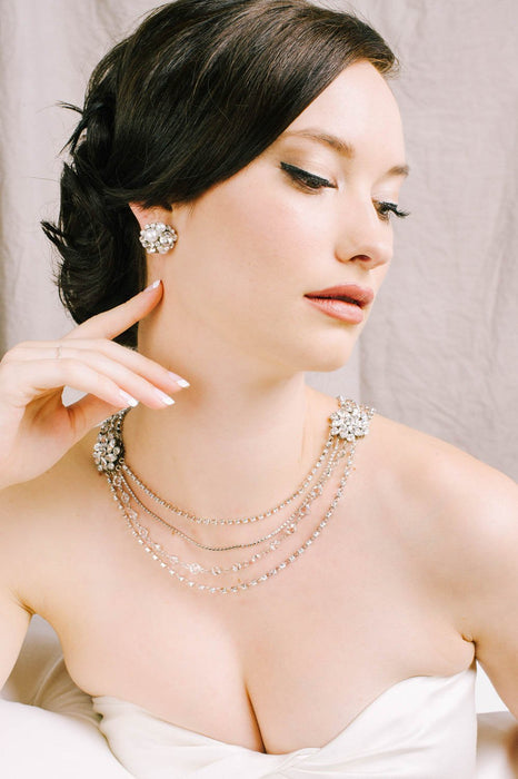 A woman wearing sparkling Swarovski and pearl stud earrings along with her multiple strand necklace that has Swarovski clear and crystal set chain and crystal embellished filigrees. Made by Sara Gabriel.