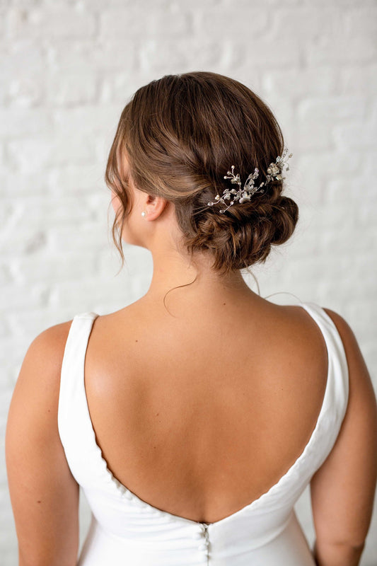 Two shimmering metal wildflower inspired hair pins that are accented with hand-wired sprigs of Swarovski crystals and pearls being worn in the back of a bride's hair. Made by Sara Gabriel.