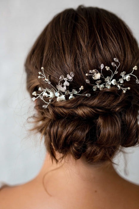 A closeup of two shimmering metal wildflower inspired hair pins that are accented with hand-wired sprigs of Swarovski crystals and pearls being worn in the back of a bride's hair. Made by Sara Gabriel.