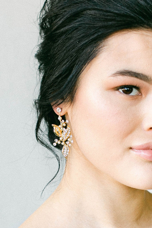 With half of her face in view, a bride is wearing a leafy designed earring that uses a gold plated metal filigree as its base, and incorporating the tiniest of Swarovski clear crystals and pale ivory pearls. This is dangled from a crystal post. Made by Sara Gabriel.
