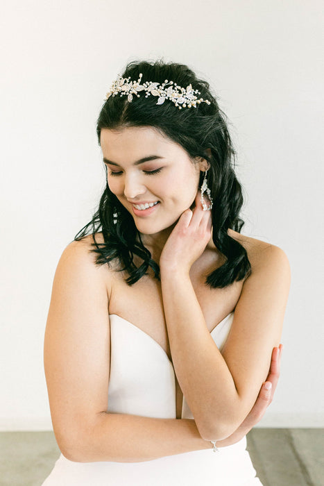 A woman in a white wedding dress wearing a botanical inspired tiara that uses leafy gold plated metal filigrees for its base. There are beaded details, which feature hand-set Swarovski crystals and pearls. Made by Sara Gabriel.