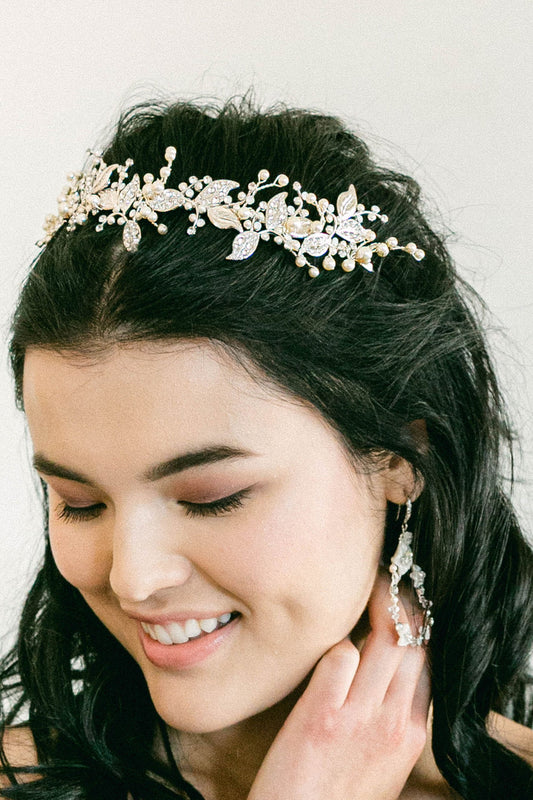 A woman wearing a botanical themed tiara that uses leafy gold plated metal filigrees for its base. There are beaded details, which feature hand-set Swarovski crystals and pearls. Made by Sara Gabriel.