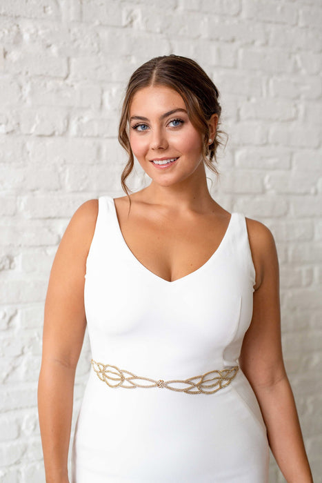 A smiling bride in a white wedding dress looking directly in the camera, wearing around her waist a hand-embroidered duet that features gold plated crystal-set chain. Sara Gabriel