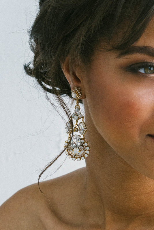 With half of her face out of view, this closeup is of a woman wearing an intricate chandelier earring that is hand-set with clear and opal Swarovski crystals. Made by Sara Gabriel.