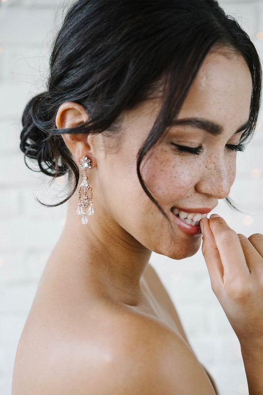 A bride with her head turned slightly, eyes closed and smiling biting her nail. She is wearing a vintage-inspired, multi-tiered rose gold plated earring. The earring incorporates three delicate crystal drops hanging from the bottom. Made with clear Swarovski crystals. Sara Gabriel