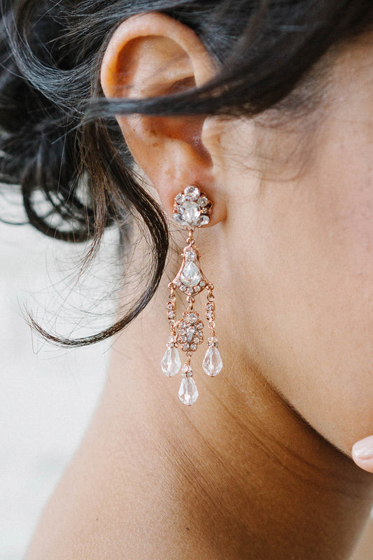 A closeup of a woman wearing a vintage-inspired multi-tier earring, which includes three delicate crystal drops dangling from the base. These earrings are made with Swarovski clear crystals of various sizes on rose gold plated filigrees. Sara Gabriel.
