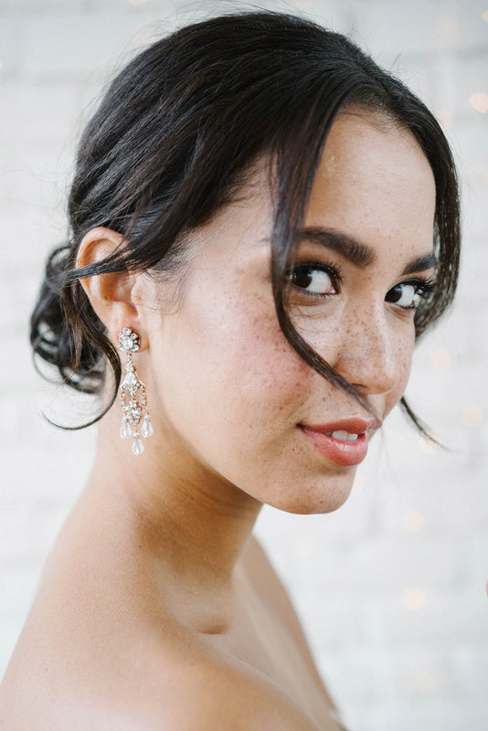 A bride with her head turned slightly, gazing into the camera. She is wearing a vintage-inspired, multi-tiered rose gold plated earring. The earring incorporates three delicate crystal drops hanging from the bottom. Made with clear Swarovski crystals. Sara Gabriel