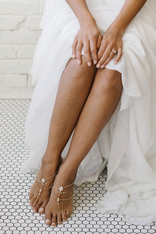 A bride with her hands in her lap, sitting down wearing a white wedding dress with only the lower half of her body visible. She is wearing foot jewelry on both feet. The foot jewelry is gold in color with a mix of clear and opal Swarovski crystals. The foot jewelry has multiple strands that go across the top of each foot. Sara Gabriel