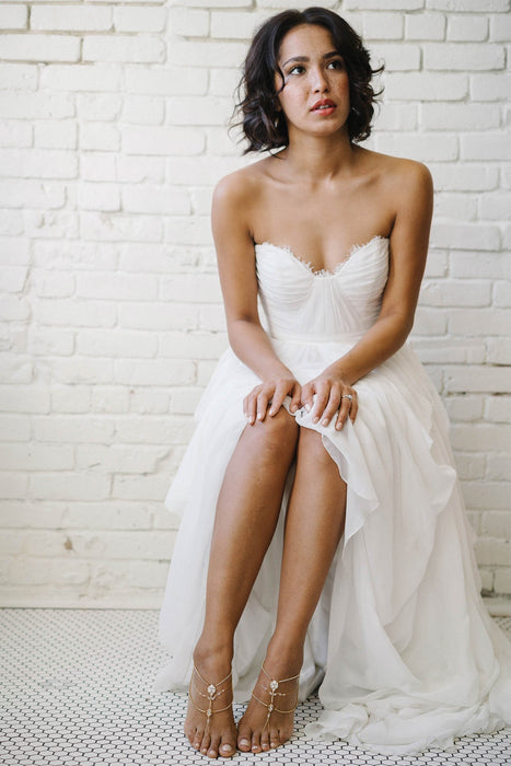 A bride sitting down in her white wedding dress, fully visible in the shot. She is looking at something out of frame. Her feet feature a piece of jewelry on each foot. The foot jewelry is multi-stranded and gold in color, but also features a mix of opal and clear Swarovski crystals. Sara Gabriel