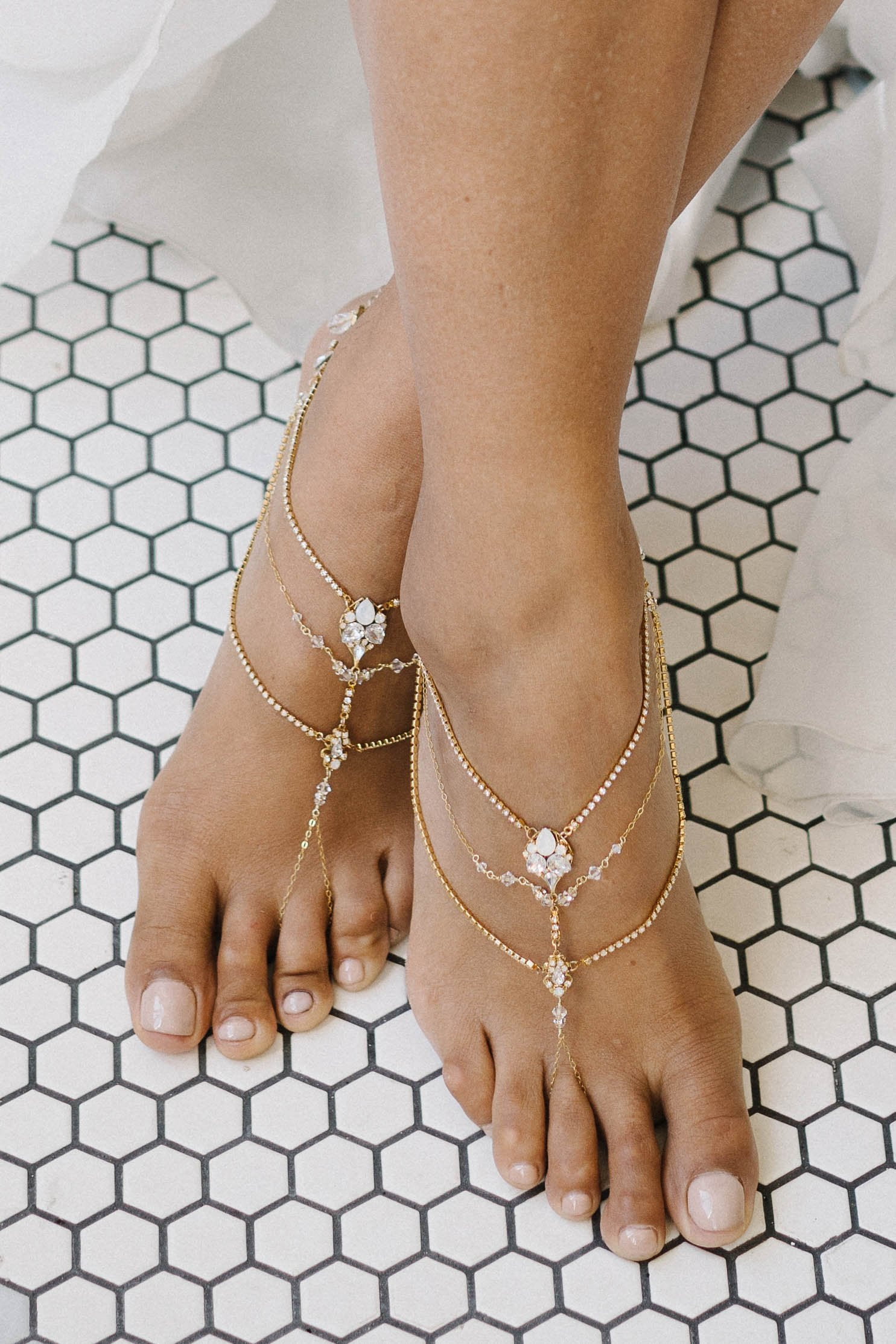 Two feet being shown wearing foot jewelry. The foot jewelry is gold in color with a mix of clear and opal Swarovski crystals. The foot jewelry has multiple strands that go across the top of each foot and each has a loop that is put over each foot's middle toe. Sara Gabriel.