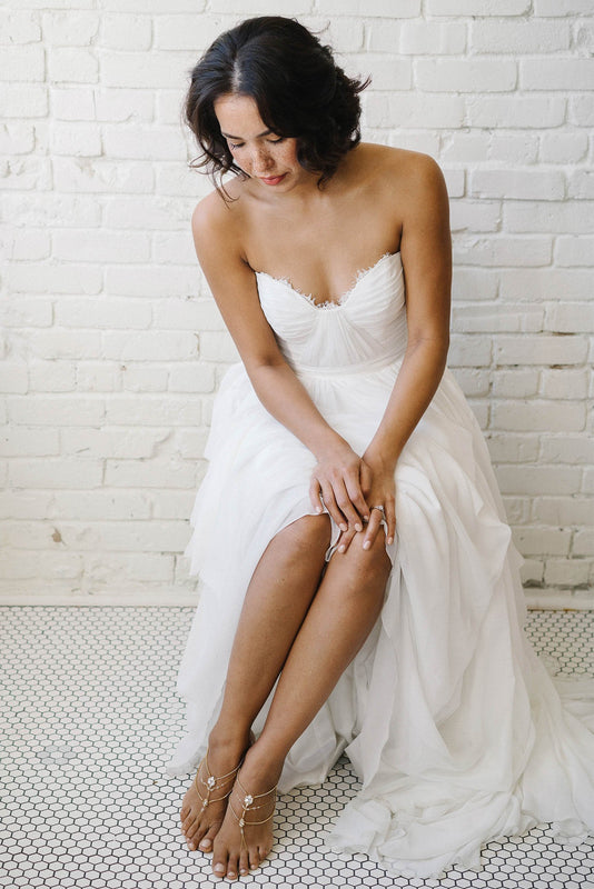 A bride sitting down in her white wedding dress, fully visible in the shot. She is staring down at her feet, which are features a piece of jewelry on each. The foot jewelry is multi-stranded and gold in color, but also features a mix of opal and clear Swarovski crystals. Sara Gabriel