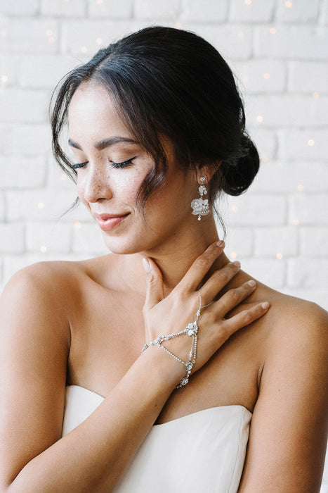 A woman with her head turned slightly to her right, eyes closed. She is wearing double drop earrings as well as hand jewelry. Both the earrings and the hand jewelry feature Swarovski opal and clear crystals and crystal-set chain. Sara Gabriel.