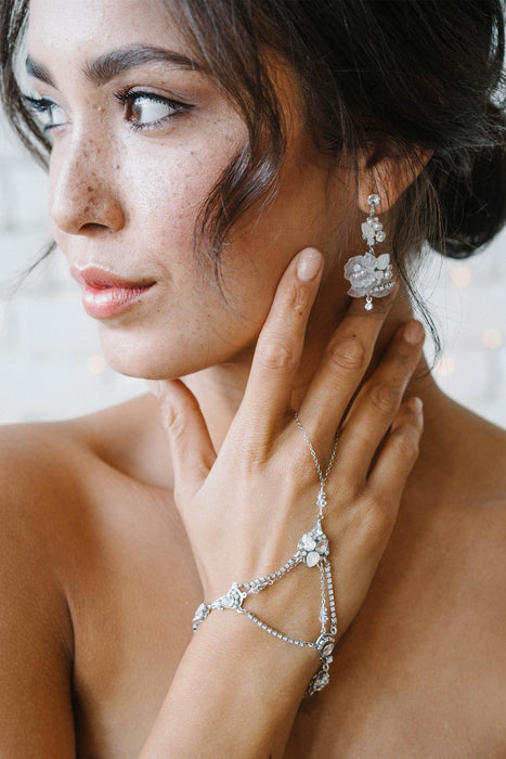 A woman looking to her right, gazing off. She is wearing double drop earrings as well as hand jewelry. Both the earrings and the hand jewelry feature Swarovski opal and clear crystals and crystal-set chain. Sara Gabriel.