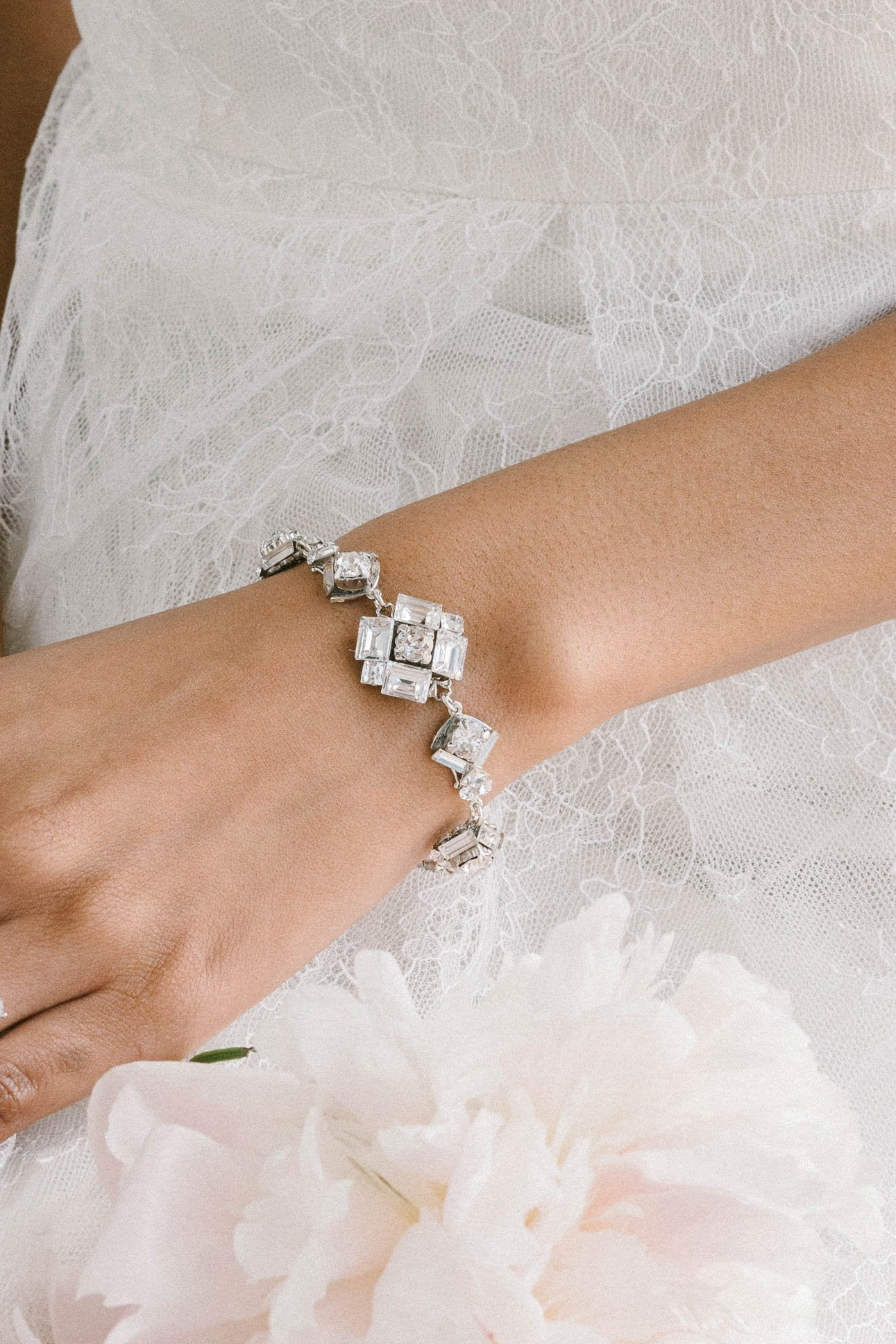 An arm is visible in the shot against a background of a wedding dress. The arm features an art deco-inspired bracelet around the wrist. It features multiple segments each of varying sizes. Each is made with clear Swarovski crystals. Sara Gabriel.