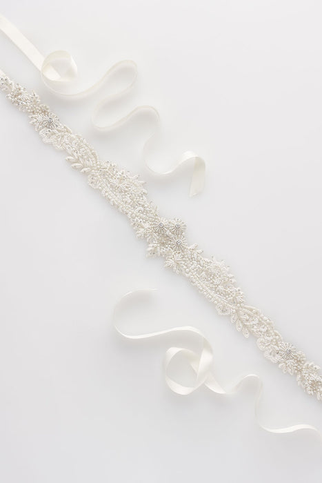 A closeup of a hand-embroidered intricate ethereal patterned sash laid out against a white background. The design features thousands of glass beads, seed pearls and Swarovski crystals. On each end of the sash there is pale ivory ribbon. Sara Gabriel