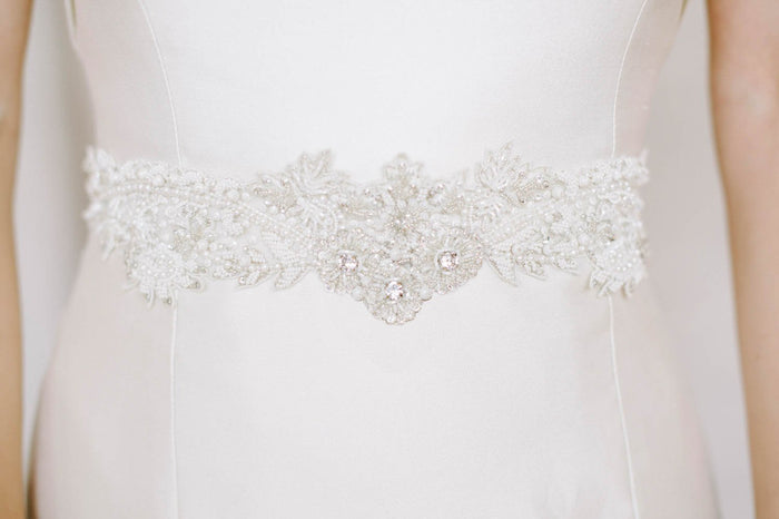 A closeup of a hand-embroidered intricate ethereal patterned sash being worn. The design features thousands of glass beads, seed pearls and Swarovski crystals. Sara Gabriel