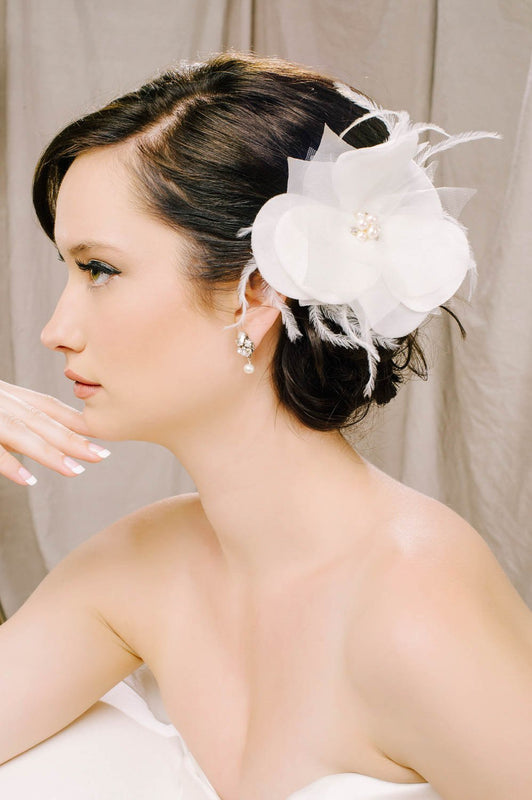 A woman turned to the right, looking ahead. In her hair, she is wearing a silk velvet organza and tulle petal hair clip. The fluttering flower-shaped clip features clusters of Swarovski crystals and freshwater pearls in the center. Soft feathers are also a feature of this clip. Sara Gabriel