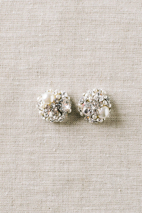A pair of vintage-inspired dome-shaped stud earrings that use clear Swarovski crystals and pale ivory pearls. Sara Gabriel