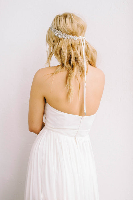 A bride turned around with her back towards the camera. In her hair, she is wearing a bridal duet that is hand-stitched into a floral-like design using silver thread-work. Made with Swarovski crystals and pearls. Sara Gabriel