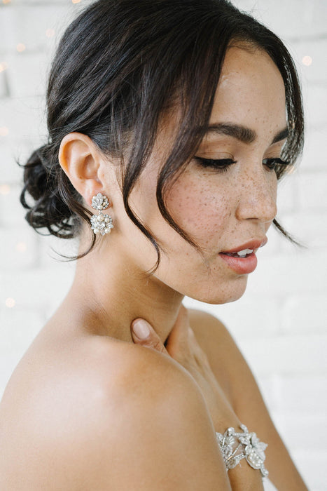 A bride with her head turned to the side, gazing away. Her right ear is sporting a vintage-inspired drop earring. The earring is made with Swarovski crystals and pearls. Sara Gabriel