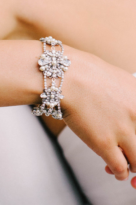 A closeup of a bracelet being worn. The bracelet consists of crystal-set chain that are woven through Swarovski clear crystals and pale ivory pearls. Sara Gabriel
