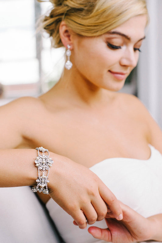 A bride sitting down and looking down. She is wearing double-drop earrings and a shimmering bracelet. The bracelet is made from crystal-set chain that is woven through Swarovski crystal and pearl encrusted filigrees. Sara Gabriel