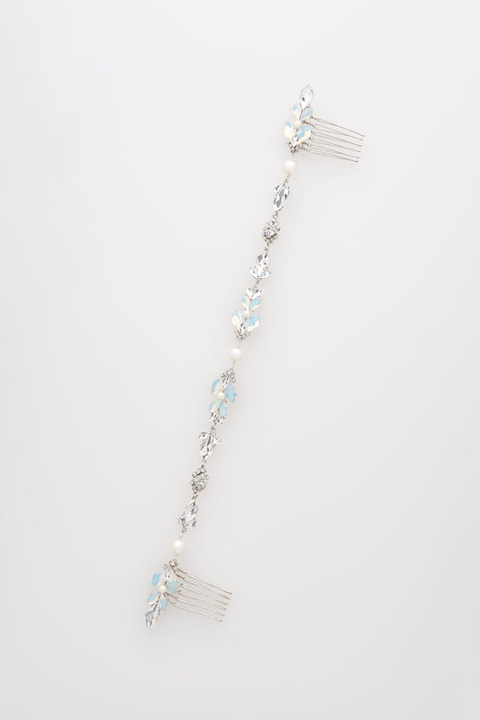 A piece of hair jewelry that is laid flat out against a white background. The hair jewelry has a six-prong comb on each side. The jewelry consists of a mix of opal and clear Swarovski crystals and diamond white pearls. Sara Gabriel
