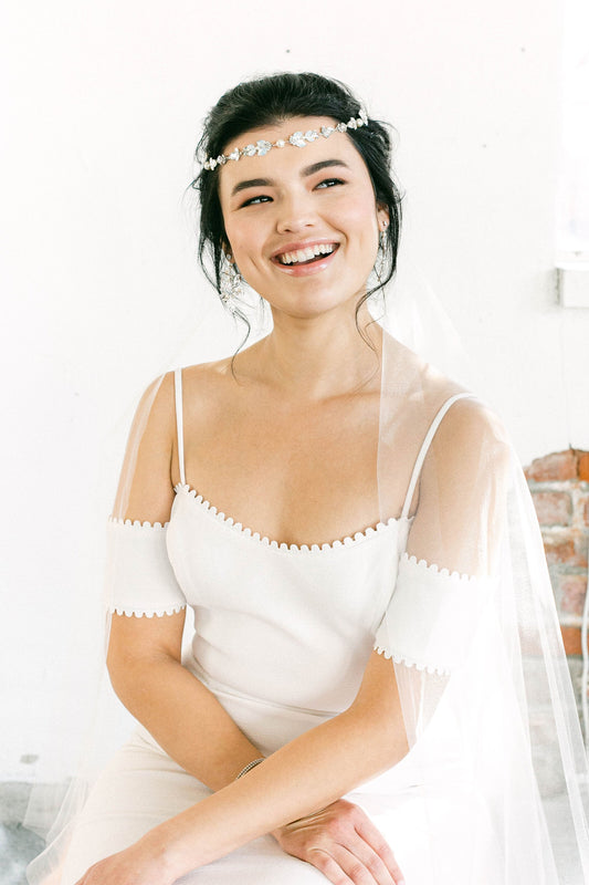 A smiling bride that is wearing a wedding veil and a white wedding dress. On her head, she is also wearing a piece of jewelry that is hanging down on her forehead for a boho vibe. The jewelry consists of a mix of opal and clear Swarovski crystals and pale ivory pearls. Sara Gabriel