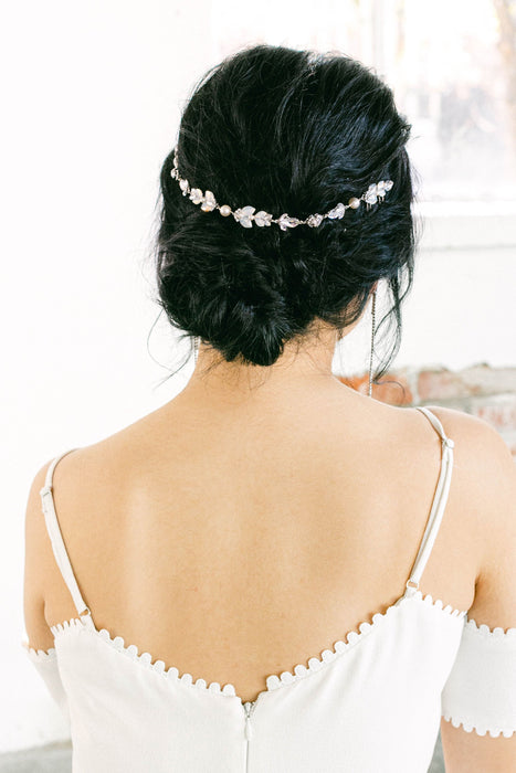 A woman with her back turned to the camera. She is wearing a bridal accessory in her hair. The hair jewelry is vintage-inspired and consists of a mix of opal and clear Swarovski crystals and pale ivory pearls. Sara Gabriel