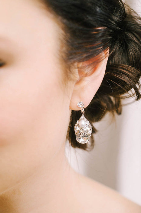 A closeup of a woman wearing an earring on her left ear, which is the only ear visible. The earring consists of clear Swarovski crystals and pearls, hanging from a crystal post. Sara Gabriel