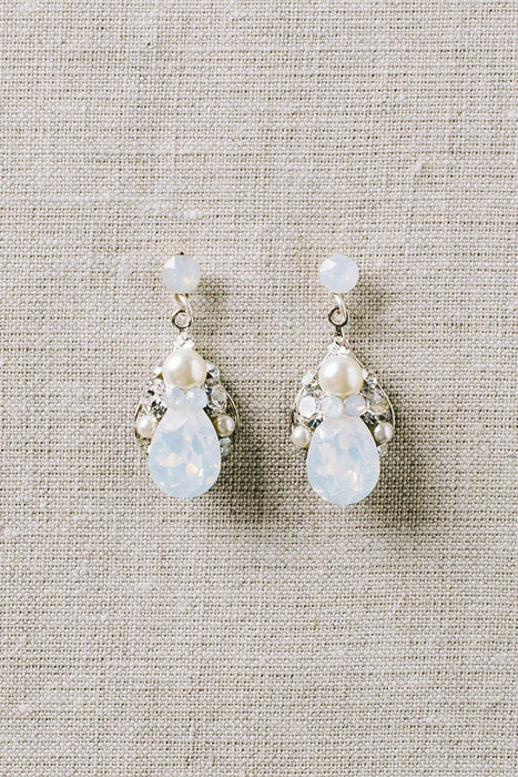 A closeup of a pair of delicate earrings that hang from a opal crystal post. The earrings consist of varying sizes of opal Swarovski crystals and pale ivory pearls. Sara Gabriel