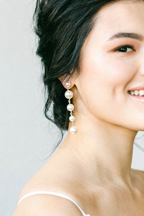 A smiling bride with half of her face in view. On her right ear, she is wearing a multi-drop pearl earrings. They are made with Swarovski pearls. Sara Gabriel