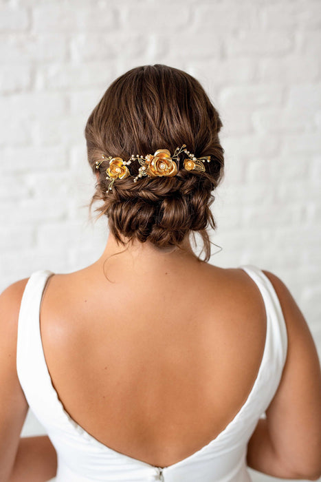 A bride with her back turned to the camera. In her hair she is wearing a set of three metal rose blossoms amidst filigree leaves and sprigs of crystals and pearls. Sara Gabriel