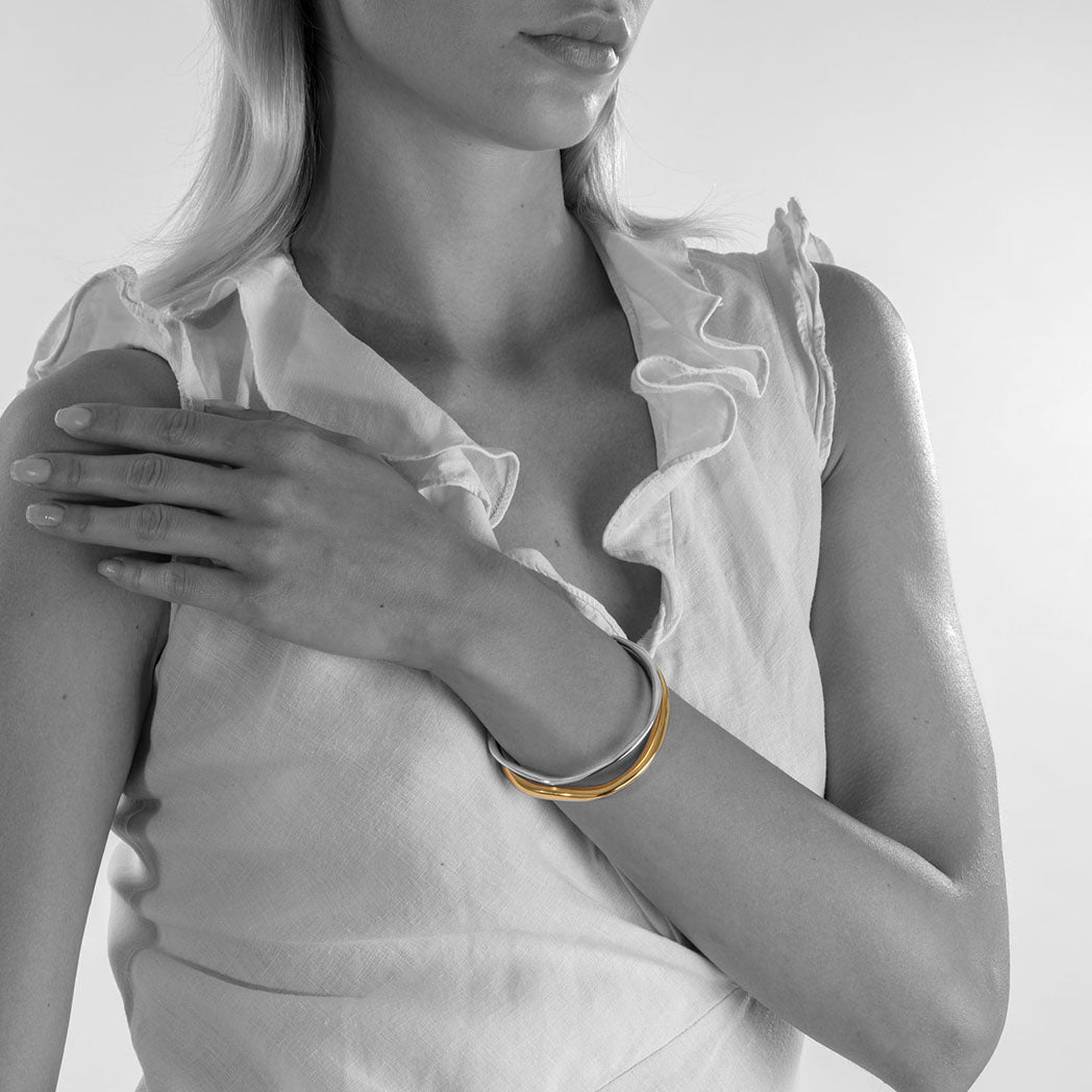 handmade ethical jewellery. organic styled thick bangle in silver and gold plated silver.