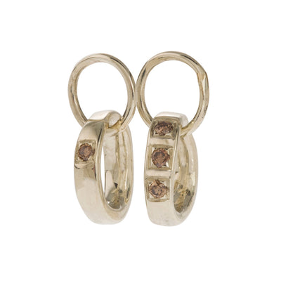 Classic, Twisted Hoop Earrings in Gold. The Classic Twist circles can be purchased plain or with diamonds. All diamonds are set in pave style framed in a squared line: three diamonds sit together on one side and one diamond on the opposite side. All diamonds are natural in colour and available in black, grey or brown, depending on the metal. The earrings come in White Gold, Yellow Gold, 18K and 9K Gold.  Edit alt text