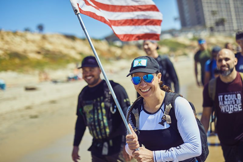 People rucking during GORUCK Challenge holding an American flag