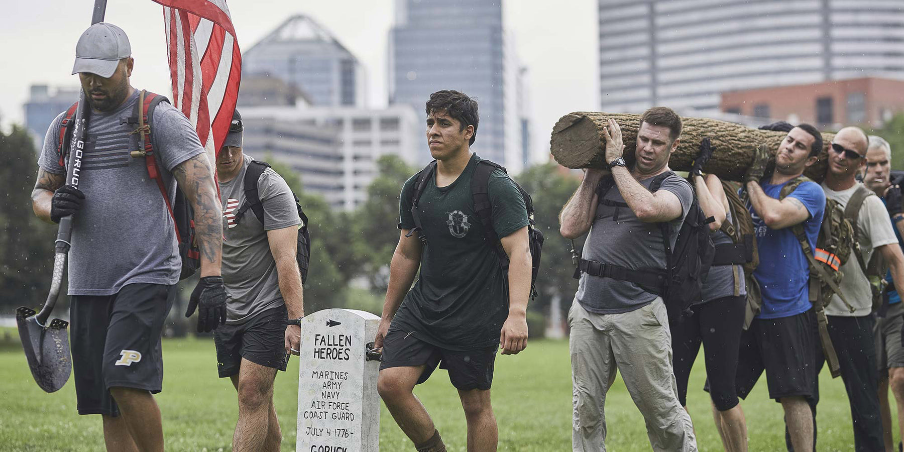 Group of people wearing rucksacks and holding a log during a GORUCK Challenge Event