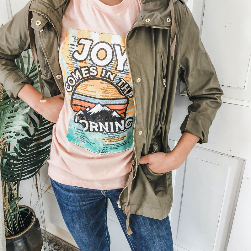 woman in green jacket and chic joy shirt