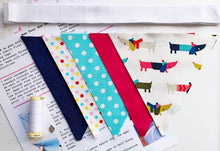 Load image into Gallery viewer, Flat lay photograph showing the contents of the kit. Instructions, cotton thread, charm, pre-cut designer fabrics, pre-cut cotton bunting tape.
