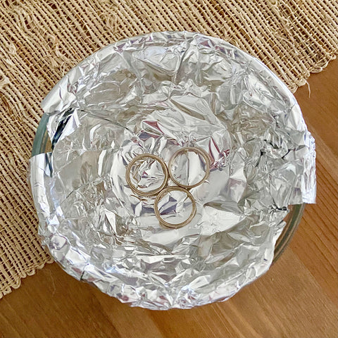 Sterling silver rings in a bowl lined with aluminum foil
