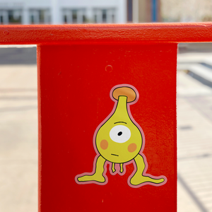 vinyl sticker depicting yellow and orange space with one eye and big feet and short arms on a red orange surface in a sunny urban city area