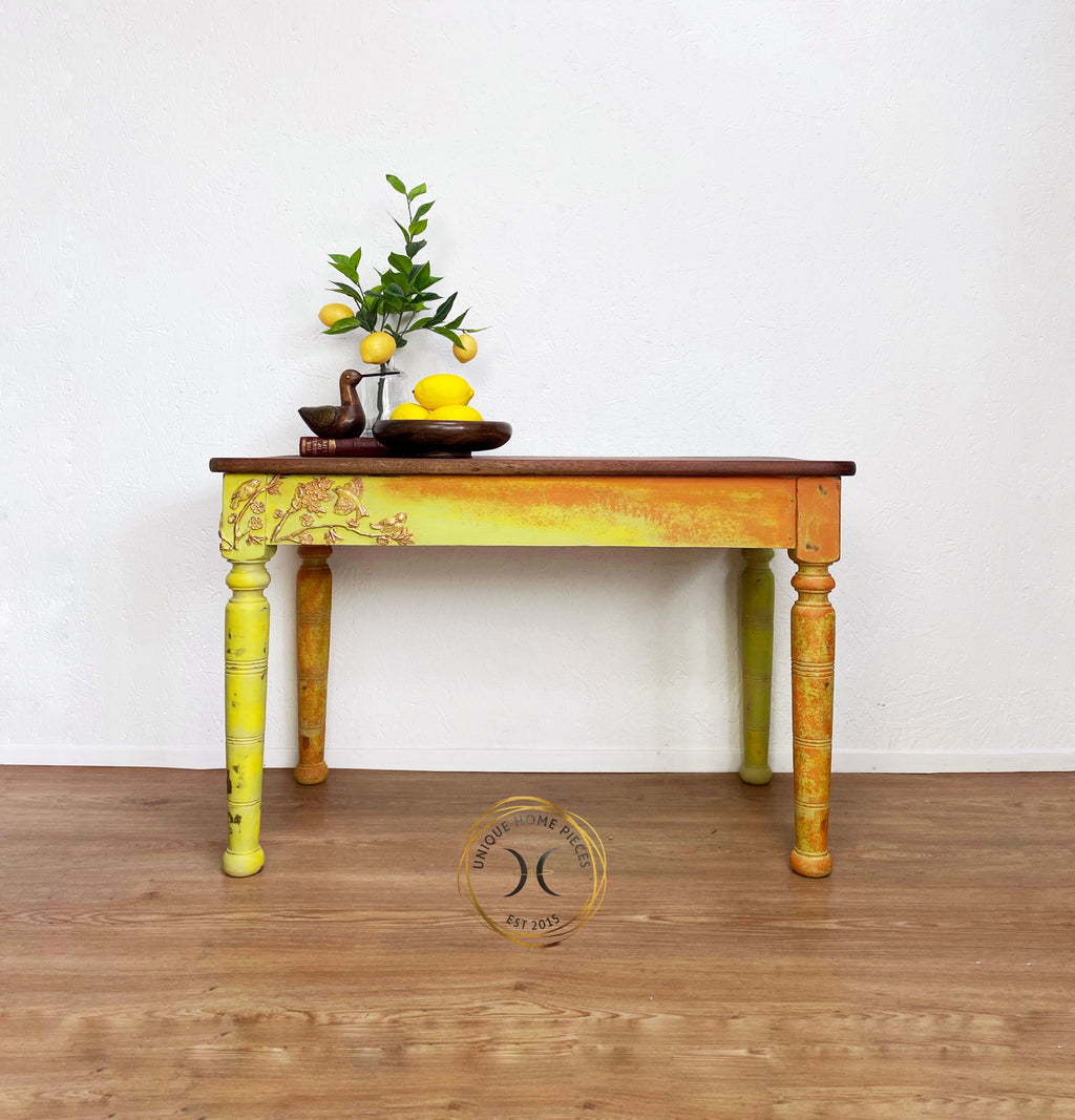 rectangular console table painted in Annie sloan chalk paint in Lem Lem, Barcelona Orange, English Yellow and Versailles, clay moulds of fauna and birds applied to the top corners of legs gold and silver gilding wax applied over the top. the top has been sanded back to reveal the grain, the top is made of a hard redwood, think it is rosewood and the table is dated back to around mid century. Height 64 cm depth 49 cm width 92 cm . this table could be used in any room at all due to it size.