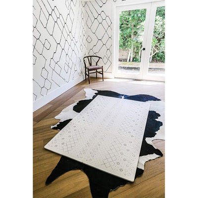 Carter Mudcloth Tan Neutral Color Play Mat Laying in a Sitting Room with a Cow Rug
