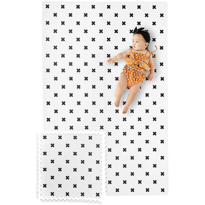 Infant Laying on Brooklyn Cross Black and White Foam Mats