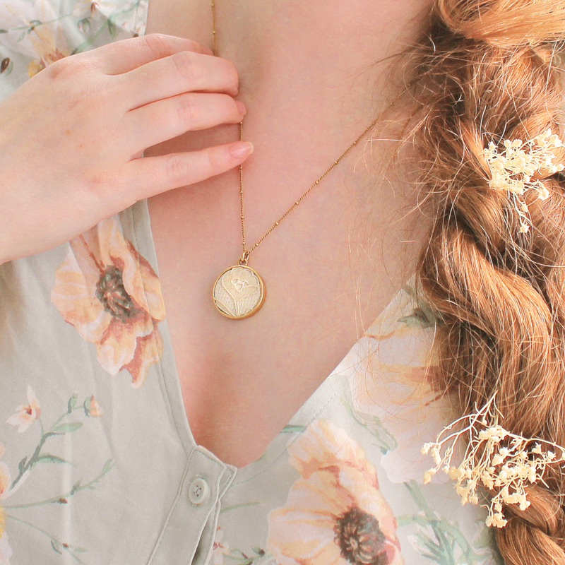 Round gold pendant necklace made from wedding dress lace, worn by model with floral dress and braided hair.